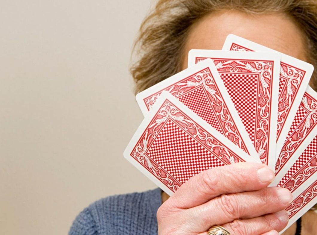 Femme cachée derrière des cartes